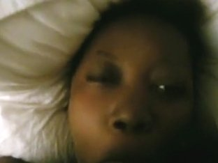 Ebony american girl lies down on the bed, while sucking cock.