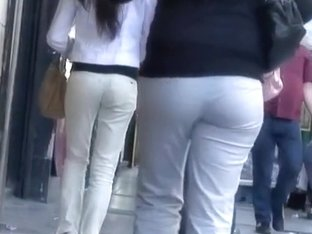 Woman in sexy pants walks on the street in front of the spy cam