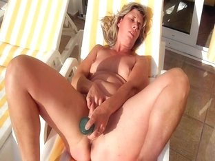 Mature woman sunbathes and masturbates the clitoris outdoor