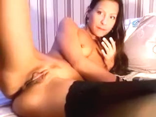 Model Bazzuka, dressed in black stockings, masturbating on the bed