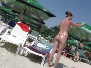 Oiled up milf sunbathes in topless