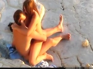 Voyeur captures a nudist couple having sex on the rocks