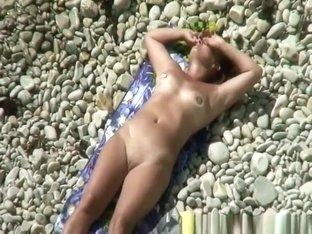 Nudist woman in rocky beach smoking