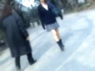 Naughty man sharking Asian college girl skirt in the street