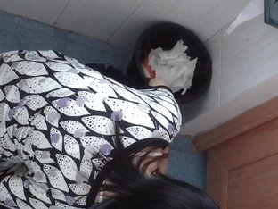 Dark-haired Asian babe pissing in the public toilet