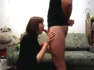 Milf deepthroats her man's cock in the living room