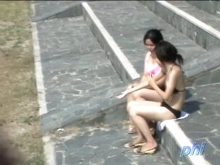 Asian babes relaxing on the beach get a boob sharking.