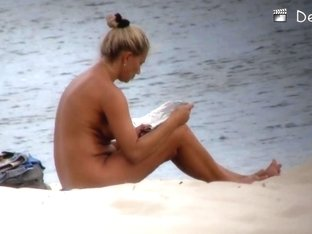 Lovely philander reading a newspaper on nudist beach