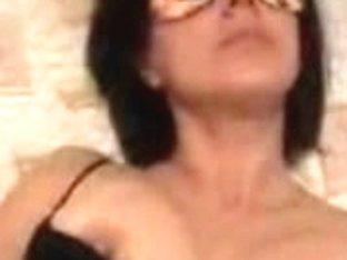 Masked mature woman stimulating her hairy vagina