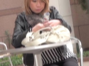 Candid street upskirt with sexy red Asian typing an sms