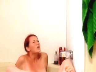 Redhead hottie masturbates with the waterbeam in the bathtub
