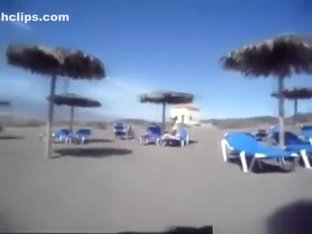 Milf gives her husband a handjob on a public nude beach