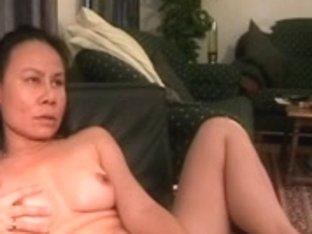 Mature Oriental wife masturbates her twat with a sex toy