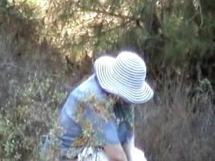 Smiling milf in big hat caught pissing outdoor