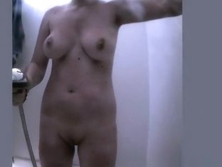 Woman showering and dressing in beach cabin