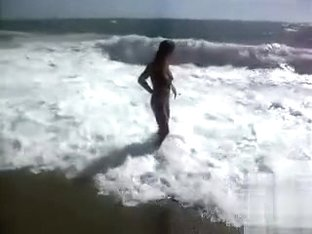Busty brunette's lower part of a bikini drops as huge waves hit her