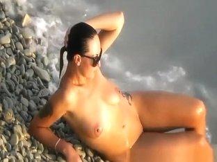 Tattooed brunette nudist wetting her feet