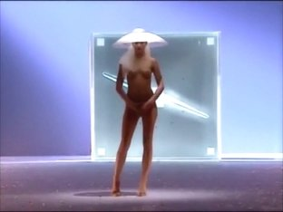 Seductive fashion model in a weird hat walks down the catwalk in the nude