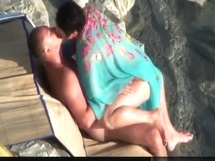 Voyeur tapes a nudist woman riding her bf at the beach