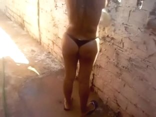 My golden-haired wife behind the fence drying her bikini panties