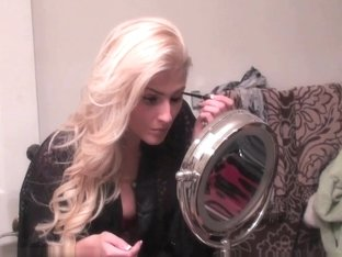 Blonde beauty puts make up on