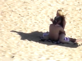 Hidden cam scene with a couple banging in the cowgirl pose on a beach