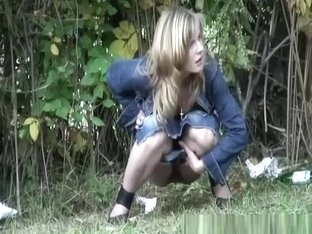 One woman in jeans skirt and other in jeans pants caught peeing