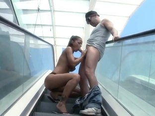 Black Angelika plays with cock on escalator