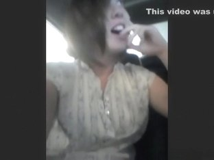 Playing with herself in her car on a parking lot