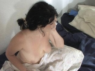 Gentle housewife talking on the phone sitting on the bed