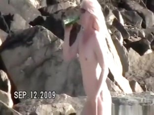 Small tits nudist at rocky beach