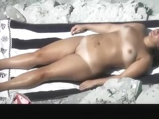 Chubby tattooed nudist woman sunbathing