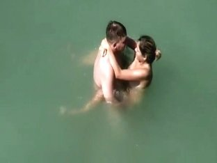 Nudist couple fucks in water