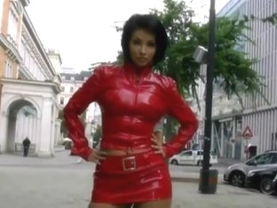 Sexy brunette girl in red pvc mini skirt and jacket