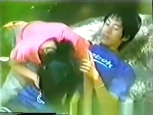 Asian girl working in her boyfriend's cock in the forest