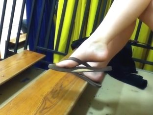 Girl dangling flip flops in the gym