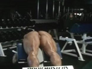 Female bodybuilder working out naked at gym