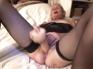 Blonde mature masturbates on a bed.