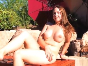 Busty babe Lulu sunbathes naked by the pool and then jumps in