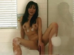 Stacked Oriental cougar Julie Koh plays with sex toys in the bathtub